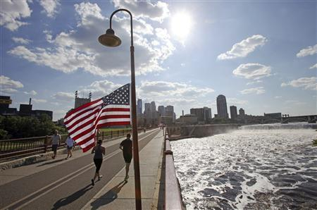 Runners cross the pedestrian-only stone arch bridge that crosses the Mississippi River downstream of the St. Anthony Falls (right) in Minneapolis, Minnesota July 3, 2013. REUTERS/Eric Miller