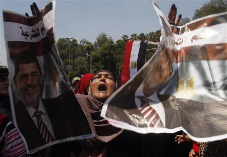 A protester, who supports former Egyptian President Mohamed Mursi, holds up posters of him during a march near Cairo University after Friday prayers in Cairo July 5, 2013. REUTERS/Asmaa Waguih