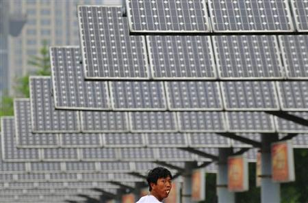 A man eats his breakfast as he walks under solar panels belonging to a solar power plant in Shenyang, Liaoning province June 5, 2013. REUTERS/Stringer