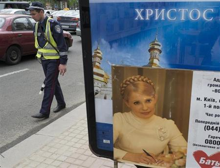 A police officer walks past a stand with jailed Ukrainian ex-prime minister Yulia Tymoshenko's photo in central Kiev April 30, 2013. REUTERS/Gleb Garanich