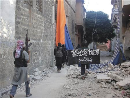 Free Syrian Army members accompanied by fighters from the Islamist Syrian rebel group Jabhat al-Nusra carry their weapons as one of them holds al-Nusra's flag while walking in the old city of Homs July 2, 2013. REUTERS/Mohamed Ibrahim/Shaam News Network/Handout via Reuters