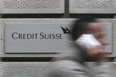 A man uses his cell phone as he walks past a branch of Swiss bank Credit Suisse in Zurich, January 31, 2012. REUTERS/Christian Hartmann