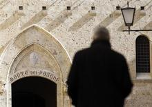 A man walks towards the main entrance of the Monte dei Paschi bank headquarters in Siena March 13, 2012. REUTERS/Max Rossi