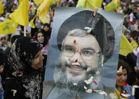 A Hezbollah supporter carries a poster of Hezbollah leader Sayyed Hassan Nasrallah during a rally marking Resistance and Liberation Day in Beirut in this May 25, 2009 file photo. REUTERS/Jamal Saidi