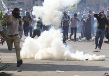 Un grupo de partidarios del ex presidente egipcio Mohamed Mursi huye de gases lacrimógenos arrojados por fuerzas de la policía en El Cairo, jul 5 2013. Al menos tres manifestantes murieron a tiros el viernes fuera de los cuarteles de la Guardia Republicana en el Cairo donde se encuentra detenido el depuesto presidente Mohamed Mursi, dijeron fuentes de seguridad, mientras airados partidarios islamistas enfrentaban a las tropas en varios puntos de Egipto. REUTERS/Louafi Larbi