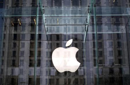 The Apple logo hangs inside the glass entrance to the Apple Store on 5th Avenue in New York City, April 4, 2013. REUTERS/Mike Segar