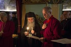 The Archbishop of Canterbury Justin Welby (3rd R) reads a blessing together with Greek Orthodox Patriarch of Jerusalem Metropolitan Theophilos (4th R) during a visit to the Church of Holy Sepulchre in Jerusalem's Old City June 28, 2013. REUTERS/Baz Ratner