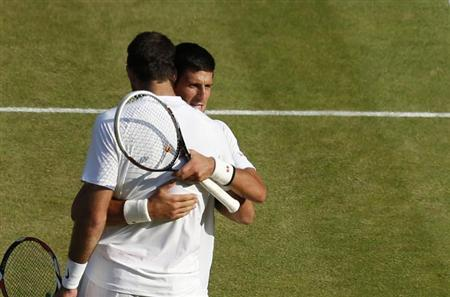 Novak Djokovic of Serbia (REAR) embraces Juan Martin del Potro of Argentina after defeating him in their men's semi-final tennis match at the Wimbledon Tennis Championships, in London July 5, 2013. REUTERS/Jonathan Brady/Pool