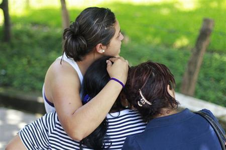 Family members hug as they look at the body of a dead man at a crime scene in Quetzaltepeque, on the outskirts of San Salvador July 5, 2013. REUTERS/Ulises Rodriguez