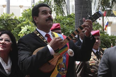 Venezuela's President Nicolas Maduro plays a Venezuelan cuatro as he arrives for a national assembly in Caracas to attend an Independence day ceremony in this July 5, 2013 handout from the Miraflores Palace. REUTERS/Miraflores Palace/Handout via Reuters