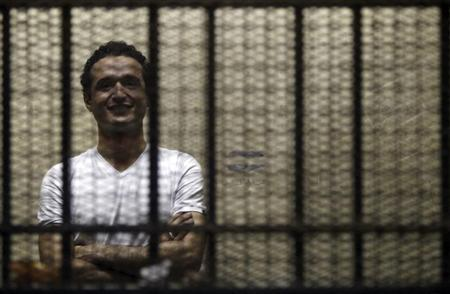 Egyptian activist Ahmed Douma stands behind bars during his trial at the New Cairo court, on the outskirts of Cairo June 3, 2013. REUTERS/Amr Abdallah Dalsh
