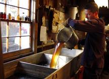 Steve Randle pours freshly made maple syrup in the finishing pan at Hollis Hills Farm in Lunenburg, Massachusetts in this February 19, 2012 file photo. REUTERS/Brian Snyder/Files