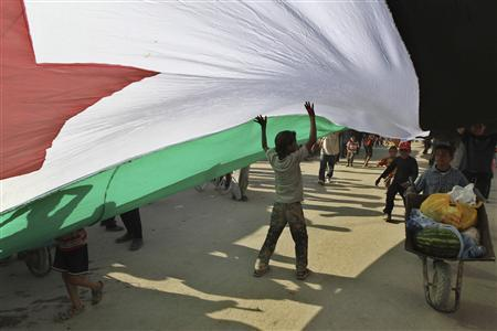 Syrian refugees hold a large Syrian opposition flag, with a length of 300 metres, to show their support for the Syrian opposition against the regime of Syrian President Bashar al-Assad at Al Zaatri refugee camp in the Jordanian city of Mafraq, near the border with Syria June 30, 2013. REUTERS/Muhammad Hamed