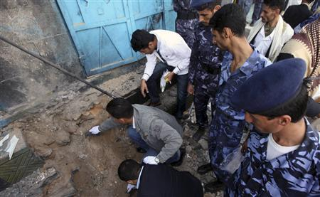 Policemen inspect the site of a roadside bomb in Sanaa July 6, 2013. REUTERS/Mohamed al-Sayaghi