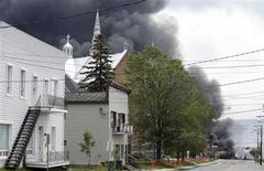 A cloud of smoke is seen over Lac Megantic after a train explosion, July 6, 2013. REUTERS/Mathieu Belanger