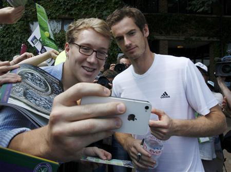 Andy Murray of Britain has a photograph taken by a fan at the Wimbledon Tennis Championships, in London July 6, 2013. REUTERS/Suzanne Plunkett