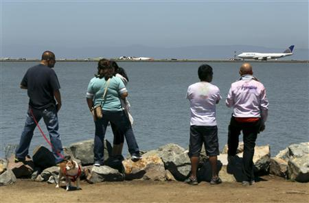 People look from a path along San Francisco Bay after an Asiana Airlines Boeing 777 that crashed while landing at San Francisco International Airport in San Francisco, California July 6, 2013. REUTERS/Robert Galbraith (UNITED STATES - Tags: DISASTER TRANSPORT)