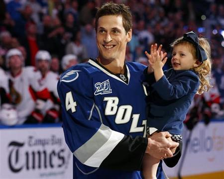 Tampa Bay Lightning's Vincent Lecavalier holds his daughter Victoria during a ceremony honoring his 1000th career NHL game before the team's NHL hockey game against the Ottawa Senators in Tampa, Florida January 25, 2013. REUTERS/Mike Carlson