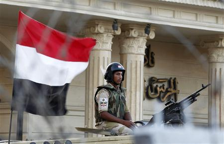 Security personnel watch over supporters of former Egyptian President Mohamed Mursi during a demonstration outside the Republican Guard building in Cairo July 6, 2013. REUTERS/Louafi Larbi