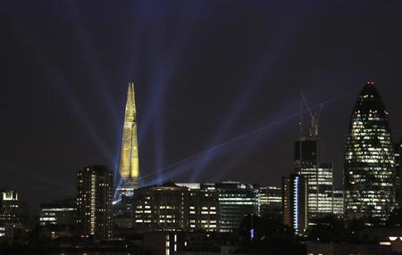 A laser beam touches the Gherkin from the Shard during the laser and searchlight show which marks the completion of the exterior of the Shard building in central London July 5, 2012. REUTERS/Olivia Harris
