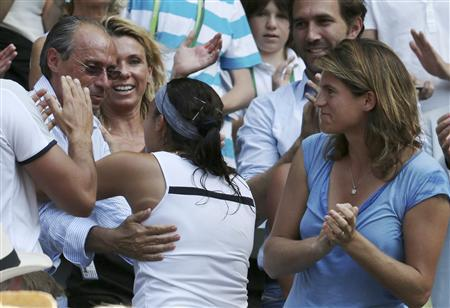 Marion Bartoli of France (C) hugs her father, Walter, after defeating Sabine Lisicki of Germany in their women's singles final tennis match at the Wimbledon Tennis Championships, in London July 6, 2013. REUTERS/Suzanne Plunkett
