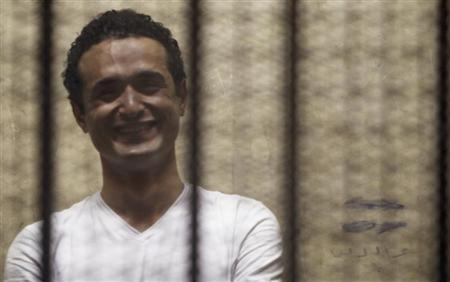 Egyptian activist Ahmed Douma smiles from behind bars during his trial at the New Cairo court, on the outskirts of Cairo June 3, 2013. REUTERS/Amr Abdallah Dalsh