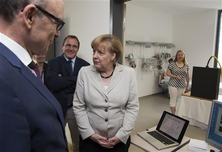 German Chancellor Angela Merkel (3rdL) listens to a presentation of a magnetic tracking system at the newly opened Life Science Campus at Greifswald University in the northern city of Greifswald, July 5, 2013. REUTERS/Thomas Peter
