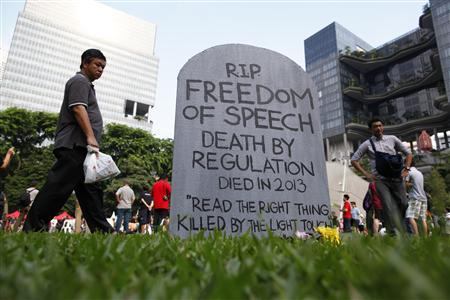 Protesters walk past a mock gravestone that reads ''RIP Freedom of Speech'' during a protest against new licensing regulations imposed by the government for online news sites, at Hong Lim Park in Singapore June 8, 2013. REUTERS/Edgar Su