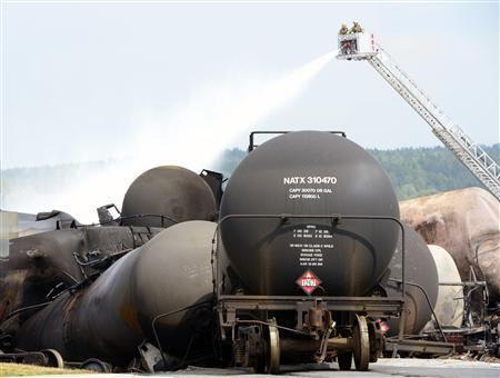 Firefighters spray water on the wreckage of the train explosion in Lac Megantic, July 7, 2013. REUTERS/Paul Chiasson/Pool