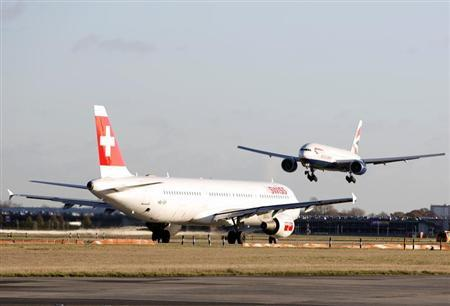 A British Airways jet approaches Heathrow Airport past a Swissair jet on the tarmac in London November 25, 2012. REUTERS/Neil Hall