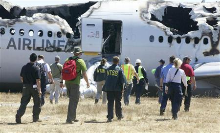 U.S. National Transportation Safety Board (NTSB) investigators work at the scene of the Asiana Airlines Flight 214 crash site at San Francisco International Airport in San Francisco, California in this handout photo released on July 7, 2013. REUTERS-NTSB-Handout