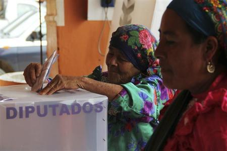A woman casts her vote in a ballot box for delegates at a polling station in San Bartolome Quialana, on the outskirts of Oaxaca, July 7, 2013. REUTERS/Jorge Luis Plata