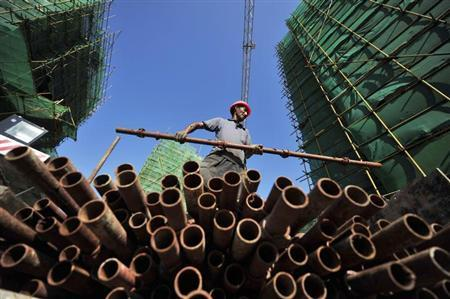 A labourer moves a steel pipe at a residential construction site in Fuzhou, Fujian province July 4, 2013. REUTERS/China Daily