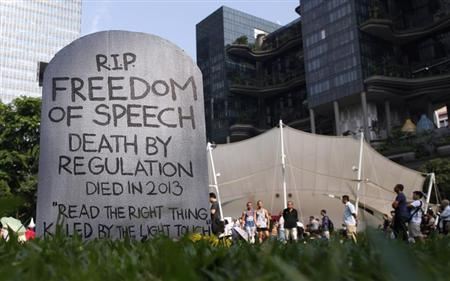 Protesters walk past a mock gravestone that reads ''RIP Freedom of Speech'' during a protest against new licensing regulations imposed by the government for online news sites, at Hong Lim Park in Singapore June 8, 2013. REUTERS/Edgar Su/Files