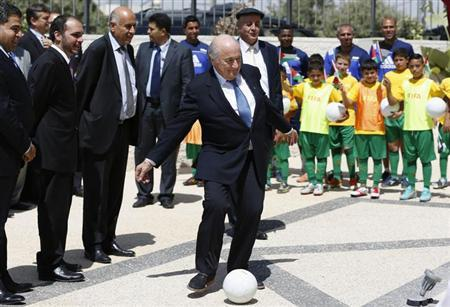 FIFA President Sepp Blatter (C) kicks a ball during the inauguration ceremony of a football academy named after him in Al-Bireh, near the West Bank city of Ramallah July 7, 2013. REUTERS/Mohamad Torokman