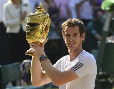 Andy Murray of Britain holds the winners trophy after defeating Novak Djokovic of Serbia in their men's singles final tennis match at the Wimbledon Tennis Championships, in London July 7, 2013. REUTERS/Toby Melville
