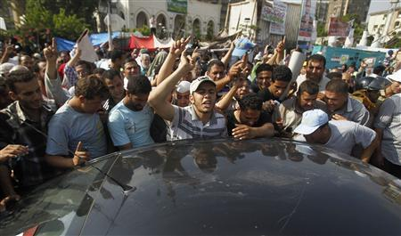 Supporters of Egypt's deposed president Mohamed Mursi gather around a car carrying the body of a fellow supporter killed by violence outside the Republican Guard headquarters in Cairo July 8, 2013. REUTERS/Khaled Abdullah