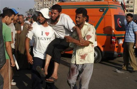 Supporters of deposed Egyptian president Mohamed Mursi help a wounded supporter outside the Republican Guard headquarters in Cairo, July 8, 2013. REUTERS/Asmaa Waguih
