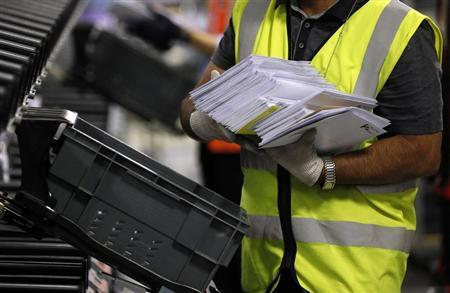 A Royal Mail employee puts sorted letters in a box at the Royal Mail Mount Pleasant Sorting Office in London May 10, 2012. REUTERS/Stefan Wermuth