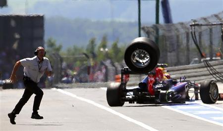 An unidentified FIA official runs over to the pits as a lost rear tyre of Red Bull Formula One driver Mark Webber of Australia bounces through the pit lane during the German F1 Grand Prix at the Nuerburgring circuit July 7, 2013. REUTERS/POOL