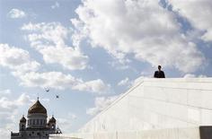 Прохожий на Патриаршем мосту в Москве 9 июня 2012 года. Летний зной немного утихнет в Москве на рабочей неделе - синоптики обещают столице чуть более прохладную погоду с переменной облачностью и редкими кратковременными дождями. REUTERS/Denis Sinyakov