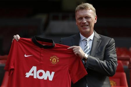 New Manchester United manager David Moyes poses with a soccer shirt in front of the home team dugout before a news conference at Old trafford in Manchester, northern England July 5, 2013. REUTERS/Phil Noble