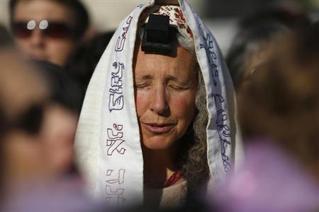 A member of ''Women of the Wall'' group wears a prayer shawl and Tefillin, leather straps and boxes containing sacred parchments, that Orthodox law says only men should don, during a monthly prayer session at the Western Wall in Jerusalem's Old City May 10, 2013. REUTERS/Amir Cohen