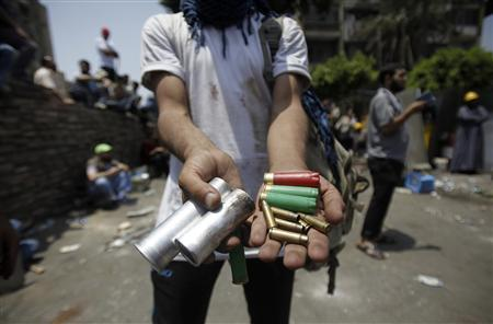 A member of the Muslim Brotherhood and supporter of deposed Egyptian President Mohamed Mursi displays spent ammunition after clashes with army in front of Republication Guard headquarters in Nasr City, in the suburb of Cairo July ,8 2013. REUTERS/Amr Abdallah Dalsh