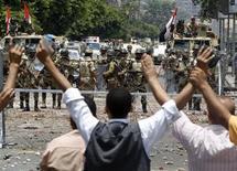 """Члены партии """"Братья-мусульмане"""", сторонники свергнутого президента Египта Мурси, выкрикивают лозунги перед армейским оцеплением вокруг штаб-квартиры национальной гвардии в городе Наср 8 июля 2013 года. Не менее 51 человека погибли в понедельник в столкновениях исламистов с военными в Каире, резко обострив ситуацию в стране, где на прошлой неделе силовиками был смещен президент-исламист, а новые власти не могут договориться о кандидатуре временного премьер-министра. REUTERS/Amr Abdallah Dalsh"""