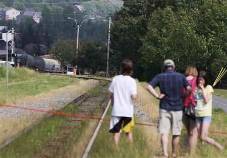 A family watches the scene of an explosion by the track that leads to derailed trains in Lac Megantic, Quebec, July 7, 2013. REUTERS/Christinne Muschi
