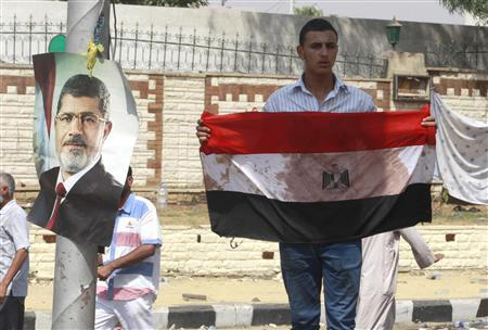 A supporter of deposed Egyptian President Mohamed Mursi holds a bloodied flag outside the Republican Guard headquarters in Cairo July 8, 2013. REUTERS/Louafi Larbi