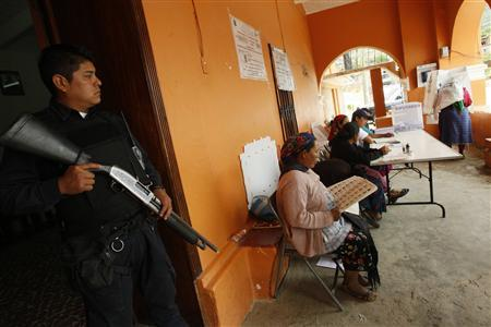 A police officer stands guard at a polling station in San Bartolome Quialana, in the outskirts of Oaxaca, July 7, 2013. REUTERS/Jorge Luis Plata
