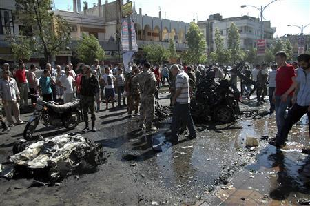 People stand at the site of an explosion in Ekrema neighborhood in Homs city July 8, 2013, in this handout photograph released by Syria's national news agency SANA. REUTERS/SANA/Handout via Reuters