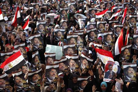 Women, who support deposed Egyptian President Mohamed Mursi, hold his posters as they rally at the Rabaa Adawia square where they are camping, in Cairo July 8, 2013. REUTERS/Khaled Abdullah